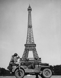 American soldiers watch the French flag flying on the Eiffel Tower, c. 25 August 1944